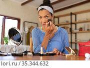 Portrait of caucasian woman applying makeup, holding makeup brush at home. Стоковое фото, агентство Wavebreak Media / Фотобанк Лори