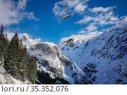 Ski lift chairs over mountain peaks and sky. Стоковое фото, фотограф Сергей Новиков / Фотобанк Лори