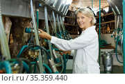 Farm milkmaid in bathrobe in barn with automatical cow milking machines. Стоковое фото, фотограф Яков Филимонов / Фотобанк Лори
