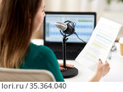 woman with microphone recording podcast at studio. Стоковое фото, фотограф Syda Productions / Фотобанк Лори