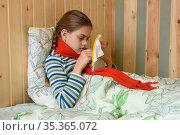 Заболевшая девочка, лежа в кровати, занимается вышивкой на пяльцах. Стоковое фото, фотограф Иванов Алексей / Фотобанк Лори