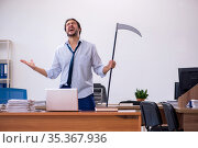 Young male furious employee holding axe in the office. Стоковое фото, фотограф Elnur / Фотобанк Лори