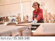 Junge Frau als Schreiner in der Ausbildung arbeitet an der Kreissäge... Стоковое фото, фотограф Zoonar.com/Robert Kneschke / age Fotostock / Фотобанк Лори