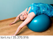 Beautiful fitness woman doing pilates exercises lying on blue fitball... Стоковое фото, фотограф Zoonar.com/OKSANA SHUFRYCH / easy Fotostock / Фотобанк Лори