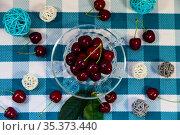 Ripe cherries in a transparent mug on a checkered napkin. Стоковое фото, фотограф Елена Блохина / Фотобанк Лори