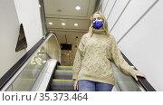 Shopping during the times of COVID-19, woman on escalator. Стоковое видео, видеограф Данил Руденко / Фотобанк Лори