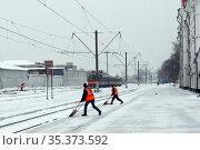 Рабочие убирают снег на платформе железнодорожной станции в Калуге (2016 год). Редакционное фото, фотограф Free Wind / Фотобанк Лори