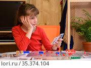 Девочка играет в настольные игры и задумалась держа в карты в руке. Стоковое фото, фотограф Иванов Алексей / Фотобанк Лори
