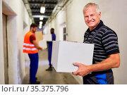 Lächelnder Arbeiter trägt Karton durch einen Gang ins Warenlager ... Стоковое фото, фотограф Zoonar.com/Robert Kneschke / age Fotostock / Фотобанк Лори