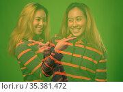 Studio shot of young Asian woman wearing hoodie against green background... Стоковое фото, фотограф Zoonar.com/Toni Rantala / easy Fotostock / Фотобанк Лори