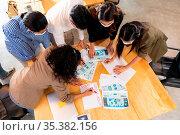 Top View Interracial asian business team brainstorming idea at office... Стоковое фото, фотограф Zoonar.com/Vichie81 / easy Fotostock / Фотобанк Лори