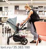 Young mom with newborn in stroller shopping at retail furniture and home accessories store wearing protective medical face mask to prevent spreading of corona virus. New normal during covid epidemic. Стоковое фото, фотограф Matej Kastelic / Фотобанк Лори