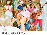 Kinder Band und Lehrerin proben zusammen für den Auftritt in der ... Стоковое фото, фотограф Zoonar.com/Robert Kneschke / age Fotostock / Фотобанк Лори