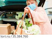 Frau mit Mundschutz hält Tasche mit Blumen in Händen vor vollem Auto... Стоковое фото, фотограф Zoonar.com/Robert Kneschke / age Fotostock / Фотобанк Лори