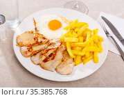 traditional spanish fried pork with fries served on blue plate on wooden table. Стоковое фото, фотограф Яков Филимонов / Фотобанк Лори