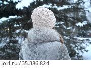 Женщина в натуральной шубе и вязаной шапке стоит спиной в зимнем лесу. Стоковое фото, фотограф Ирина Борсученко / Фотобанк Лори