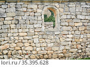 Stone wall of an ancient building with a semicircular window, beyond which other ruins are visible. Стоковое фото, фотограф Евгений Харитонов / Фотобанк Лори