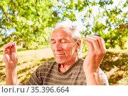 Entspannter Senior mit geschlossenen Augen bei einer Atemübung als... Стоковое фото, фотограф Zoonar.com/Robert Kneschke / age Fotostock / Фотобанк Лори
