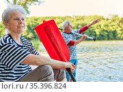 Senioren Paar sitzt entspannt am See Ufer mit Ruder vom Ruderboot... Стоковое фото, фотограф Zoonar.com/Robert Kneschke / age Fotostock / Фотобанк Лори