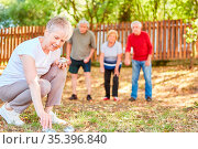 Gruppe Senioren als Rentner beim Boule spielen im Garten bei einem... Стоковое фото, фотограф Zoonar.com/Robert Kneschke / age Fotostock / Фотобанк Лори