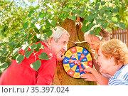 Drei Senioren beim Dartspiel an der Wurfscheibe zählen Punkte im ... Стоковое фото, фотограф Zoonar.com/Robert Kneschke / age Fotostock / Фотобанк Лори