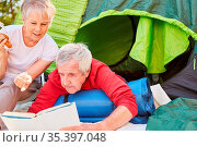 Rentner Senioren Paar entspannt sich beim Lesen vor dem Zelt im Outdoor... Стоковое фото, фотограф Zoonar.com/Robert Kneschke / age Fotostock / Фотобанк Лори