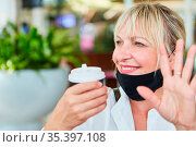 Lächelnde Frau mit Mundschutz am Kinn im Cafe winkt zur Begrüßung... Стоковое фото, фотограф Zoonar.com/Robert Kneschke / age Fotostock / Фотобанк Лори