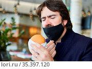 Mann mit Mundschutz am Kinn wegen Covid-19 im Restaurant beim Burger... Стоковое фото, фотограф Zoonar.com/Robert Kneschke / age Fotostock / Фотобанк Лори