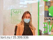 Frau als Verkäufer oder Kellnerin mit Mundschutz bei Covid-19 Pandemie. Стоковое фото, фотограф Zoonar.com/Robert Kneschke / age Fotostock / Фотобанк Лори