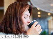 Frau als Gast mit Maske am Kinn wegen Covid-19 Pandemie trinkt Kaffee... Стоковое фото, фотограф Zoonar.com/Robert Kneschke / age Fotostock / Фотобанк Лори