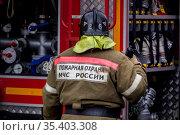Сотрудник пожарного расчета стоит у пожарной машины во время тушения пожара в центре города Москвы, Россия. Редакционное фото, фотограф Николай Винокуров / Фотобанк Лори