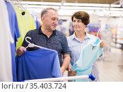 Mature couple husband and wife choose tshirts in supermarket. Стоковое фото, фотограф Татьяна Яцевич / Фотобанк Лори