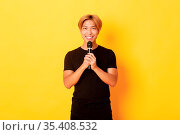 Portrait of charismatic smiling asian man holding microphone and singing... Стоковое фото, фотограф Zoonar.com/Phongthorn Hiranlikhit / easy Fotostock / Фотобанк Лори