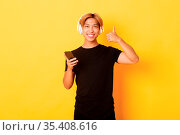 Happy satisfied asian guy likes music or podcast, showing thumbs-up... Стоковое фото, фотограф Zoonar.com/Phongthorn Hiranlikhit / easy Fotostock / Фотобанк Лори