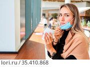 Genervte Frau mit Mundschutz am Kinn wegen Covid-19 Pandemie mit ... Стоковое фото, фотограф Zoonar.com/Robert Kneschke / age Fotostock / Фотобанк Лори