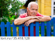 gray haired man in red pollo posing near a blue fence in the village. Стоковое фото, фотограф Татьяна Яцевич / Фотобанк Лори