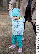 Smiling enjoying kid learning to walk with mother assistance, family relation. Стоковое фото, фотограф Кекяляйнен Андрей / Фотобанк Лори