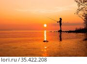 Woman fishing on Fishing rod spinning at sunset background. Стоковое фото, фотограф Zoonar.com/Andrey Armyagov / easy Fotostock / Фотобанк Лори
