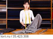 Saleswoman offering cloth in textile shop. Стоковое фото, фотограф Яков Филимонов / Фотобанк Лори