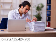 Young businessman employee unhappy with excessive work in the of. Стоковое фото, фотограф Elnur / Фотобанк Лори