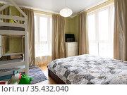 Интерьер спальной комнаты с большой двухспальной кроватью, двухъярусной детской кроваткой и двумя большими витражными окнами. Стоковое фото, фотограф Иванов Алексей / Фотобанк Лори
