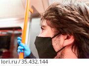 Mann als Fahrgast mit Mundschutz wegen Covid-19 Pandemie in Bus und... Стоковое фото, фотограф Zoonar.com/Robert Kneschke / age Fotostock / Фотобанк Лори