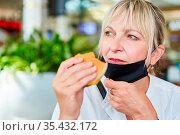 Frau als Gast mit Mundschutz am Kinn beim Burger essen im Fast Food... Стоковое фото, фотограф Zoonar.com/Robert Kneschke / age Fotostock / Фотобанк Лори