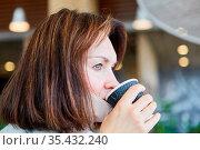 Frau mit Mundschutz am Kinn wegen Covid-19 Pandemie beim Kaffee trinken. Стоковое фото, фотограф Zoonar.com/Robert Kneschke / age Fotostock / Фотобанк Лори
