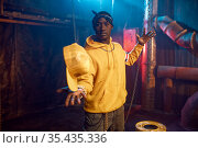 Stylish rapper in yellow hoodie poses in studio. Стоковое фото, фотограф Tryapitsyn Sergiy / Фотобанк Лори