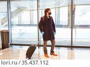 Geschäftsreisender mit Koffer und Mundschutz wegen Covid-19 Pandemie... Стоковое фото, фотограф Zoonar.com/Robert Kneschke / age Fotostock / Фотобанк Лори