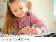 Kind hält roten Stift in der Hand zum Malen. Стоковое фото, фотограф Zoonar.com/Robert Kneschke / age Fotostock / Фотобанк Лори