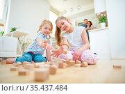 Zwei Kinder werfen Bausteine um beim Spielen zu Hause. Стоковое фото, фотограф Zoonar.com/Robert Kneschke / age Fotostock / Фотобанк Лори