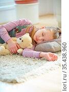 Mädchen schläft mit ihrem Kuscheltier auf dem Boden. Стоковое фото, фотограф Zoonar.com/Robert Kneschke / age Fotostock / Фотобанк Лори