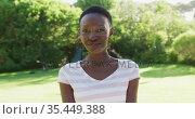 Portrait of african american woman standing in sunny garden smiling to camera. Стоковое видео, агентство Wavebreak Media / Фотобанк Лори
